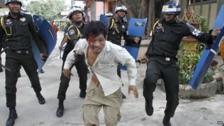 An injured Cambodian worker escapes from riot police in the compound of a Buddhist pagoda in Phnom Penh, Cambodia, Tuesday, Nov. 12, 2013
