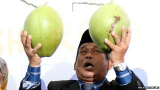 """A Malaysian """"Bomoh"""" holding two pieces of fruit"""
