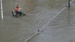 Woman sitting in floodwater