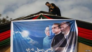 Supporter of Afghan presidential candidate Zalmai Rassoul hangs poster.