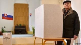 A man prepares to cast his ballot at a polling station during the first round presidential elections in Bratislava March 15, 2014.