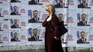 A woman walks past election posters in Belgrade. Photo: 15 March 2014