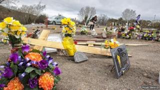 Wooden crosses have been pulled up from recently filled graves during the attacks at Monks Hill Cemetery