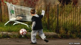 Child playing football near shopping trolley