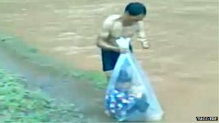 Man putting child into a bag near river