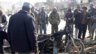 An Afghan police officer stands at the site of a suicide blast in Maymana, Faryab, northern Afghanistan on 18 March 2014