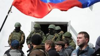 Russian soldiers and pro-Russian self-defence activists patrol at the Ukrainian navy headquarters in the Crimean city of Sevastopol