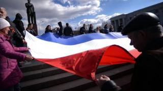 Demonstrators hold a Russian flag in the Crimean city of Simferopol on 18 March, 2014.