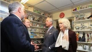 The Prince and Camilla are shown teapots on display in the museum of Teapot Island