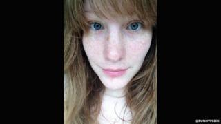 A woman wearing no makeup takes a selfie