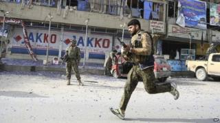 An Afghan army soldier runs into position next to the partly destroyed offices of a TV station