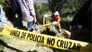 Police tape is seen around a cordoned off area where forensic technicians work during an exhumation at a hidden mass grave discovered in Lourdes, El Salvador