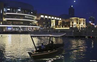 People travel on a boat in an artificial lake at Dubai Mall area in Dubai (15 March 2014)