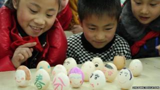 Children balance eggs on a table