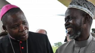 Bangui's archibishop Dieudonne Nzapalainga (L) talks with President of the Muslim community of Central Africa Imam Omar Rabine Layama (R) upon their arrival at Bangassou airport, on October 8, 2013 in Bangassou, to meet members of the Christian and Muslim communities after a week of tension