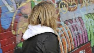 Girl in front of wall covered in graffiti