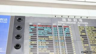 International arrivals board shows Malaysia Airlines Flight MH370 as being delayed