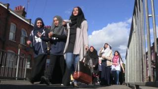 Asian women walking to Kenilworth Road football ground