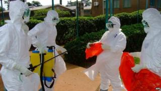 File photo of officials from the World Health Organization in protective clothing preparing to enter Kagadi Hospital in Kibale District, about 200 kilometres from Kampala, where an outbreak of Ebola virus started (28 July 2012)