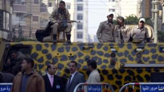 Police officers deployed outside the Minya Central Court on 25 March 2014