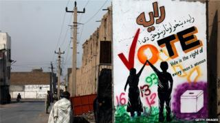 An Afghan pedestrian walks past a wall decorated with an election mural in Kandahar