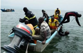Uganda Police divers and local fishermen, on a boat, search for victims of a boat disaster on Lake Albert