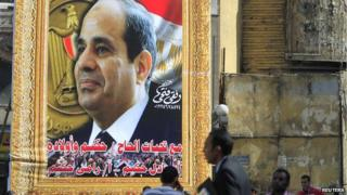 People walk past a banner for Egypt's army chief Field Marshal Abdel Fattah al-Sisi in downtown Cairo on 26 March 2014.