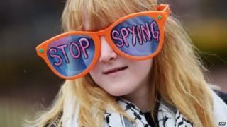 US woman wears large sunglasses with a 'Stop spying' message during an anti-government surveillance rally in Washington (28 March 2014)