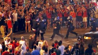 A man is taken into police custody tried to disperse a crowd of University of Arizona fans in Tucson on 29 March.