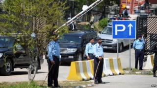 Pakistani police stand guard as the vehicle (C) carrying former military ruler Pervez Musharraf leaves a special court after a hearing in Islamabad on March 31, 2014.
