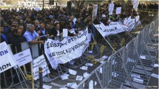 Demonstrators hold signs and banners outside Cyprus's parliament as they protest plans by the government in Nicosia 27/02/14.