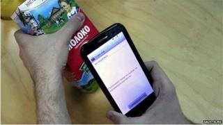 A man uses the Boycott the Occupiers app to see where a packet of milk has come from