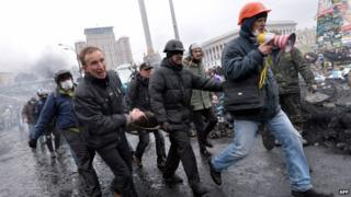 Anti-government protesters carry a wounded demonstrator in Kiev. Photo: 20 February 2014
