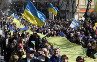 Demonstrators carry a huge Ukrainian national flag during an anti-war protest in the Black Sea port of in Odessa, Ukraine, Sunday, March 30, 2014.