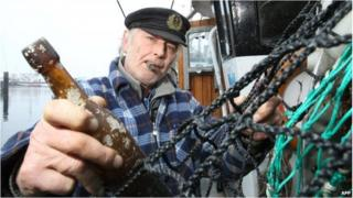 A fisherman holds the world's oldest letter in a bottle
