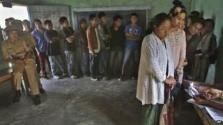 People stand in line to cast their votes inside a polling booth at Senapati, in Manipur state, India, , April 9, 2014