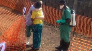 Rose Komano, who has recovered from Ebola, is hugged by a nurse in Guinea