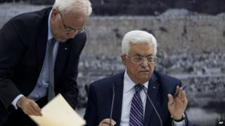 Palestinian President Mahmoud Abbas, right, joined by Palestinian chief peace negotiator Saeb Erekat, signs an application to the UN agencies in the West Bank city of Ramallah, on 1 April 2014.