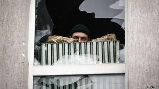 A pro-Russian protester looks out of the window of a seized office of the Ukrainian state security service in Luhansk, in eastern Ukraine, on 11 April 2014