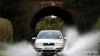 Car driving through water on rural road