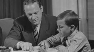 A 1940 photograph of a father helping his son do homework.