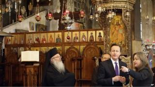David Cameron talks to officials as he visits the Church of the Nativity in the West Bank town of Bethlehem on Thursday, March 13, 2014