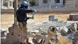 A member of a UN investigation team taking samples near the site of a 2012 chemical attack