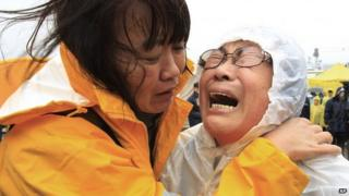 Relatives of a passenger aboard a sunken ferry weep as they wait for news on the rescue operation, at a port in Jindo, South Korea, 17 April 2014