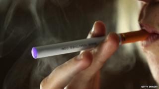 A a close-up photograph of a woman smoking an e-cigarette.