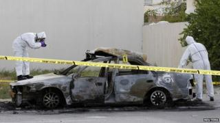 A police forensic team collect evidence at the scene of a car explosion in a village near Manama, Bahrain - 19 April 2014