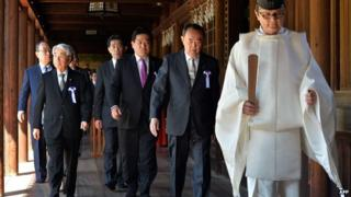 Japanese lawmakers follow a Shinto priest during a visit to the controversial Yasukuni shrine to honour the war dead at shrine's spring festival in Tokyo on 22 April, 2014