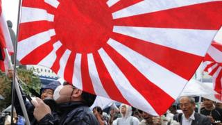 This picture taken on 23 September 2012 shows members of a right wing group raising Japan's rising sun flag during a rally in Tokyo
