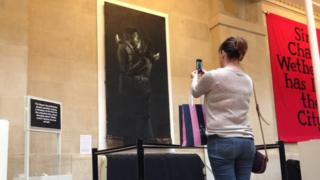 A woman photographing Mobile Lovers on her phone