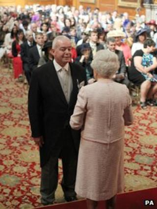 The Queen presents Richard Hook with his ambulance service medal
